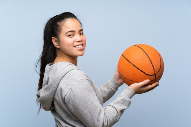 Young asian girl playing basketball over isolated wall