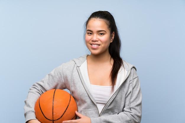 Young asian girl playing basketball over isolated wall