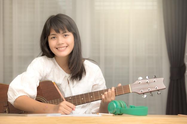Молодая азиатская девушка играет на гитаре и пытается быть музыкальным композитором, автором песен