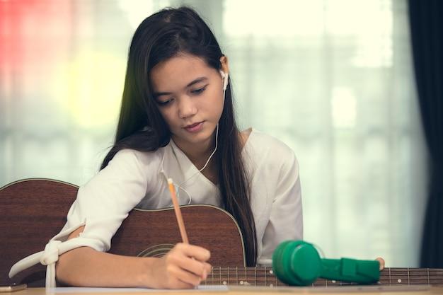 기타를 연주하고 음악 작곡가, 작곡가를 시도하는 젊은 아시아 소녀