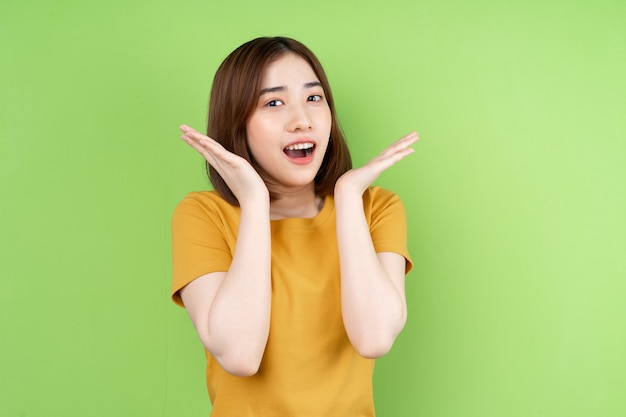 緑の背景にポーズをとって若いアジアの女の子