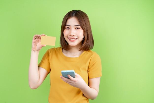 녹색 배경에 포즈 젊은 아시아 소녀