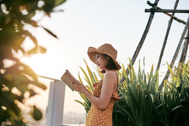 Молодая азиатская девушка читает на природе под летним солнцем