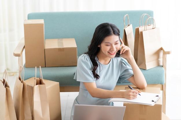 オンラインで販売している家に座っている若いアジアの女の子