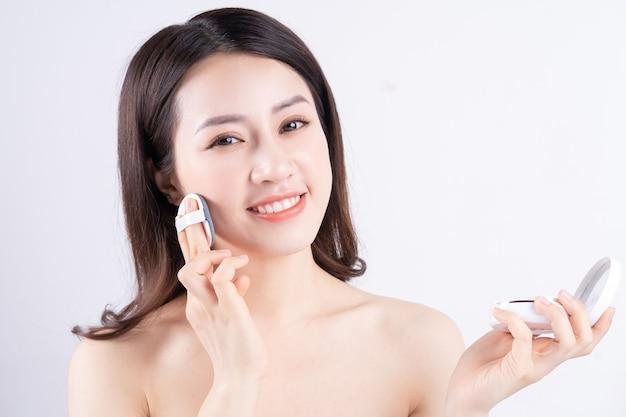 幸せな顔で化粧の箱を持って座っている若いアジアの女の子