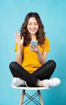 ターコイズブルーの陽気な表情で電話を使用して椅子に座っている若いアジアの女の子