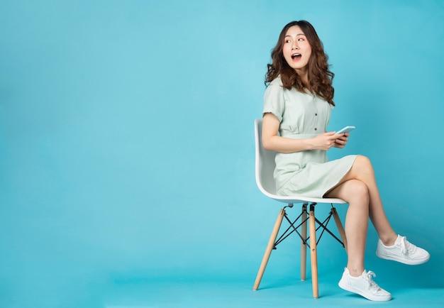 ターコイズブルーの驚きの表情で電話を使用して椅子に座っている若いアジアの女の子