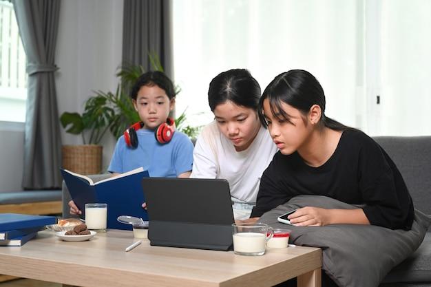 コンピューター タブレットを使用してリビング ルームのソファに座って、余暇の週末を一緒に楽しむ若いアジアの女の子。