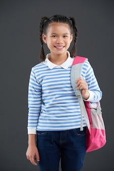 Giovane ragazza asiatica in maglione a strisce che posa con lo zaino su una spalla