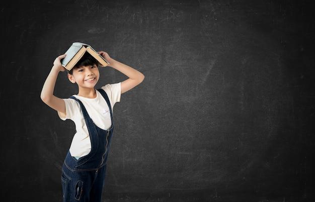 黒板背景に頭の上の本を持って若いアジア女子生徒