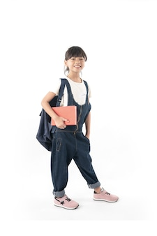 Young asian girl student holding book with school bag isolated on white background