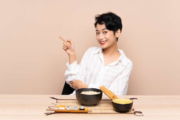 Young asian girl in a table with bowl of noodles and sushi pointing finger to the side