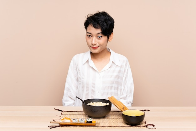 Young asian girl in a table with bowl of noodles and sushi standing and looking to the side