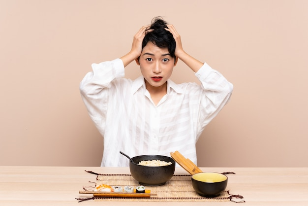 Young asian girl in a table with bowl of noodles and sushi with surprise facial expression