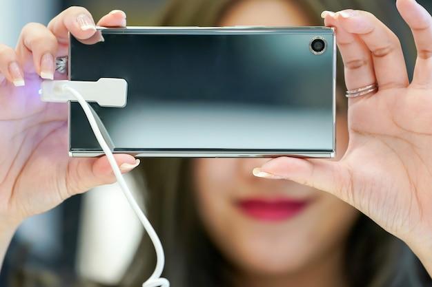 Молодая азиатская девушка тестирует и играет в новый мобильный телефон в магазине электронных сотовых телефонов.