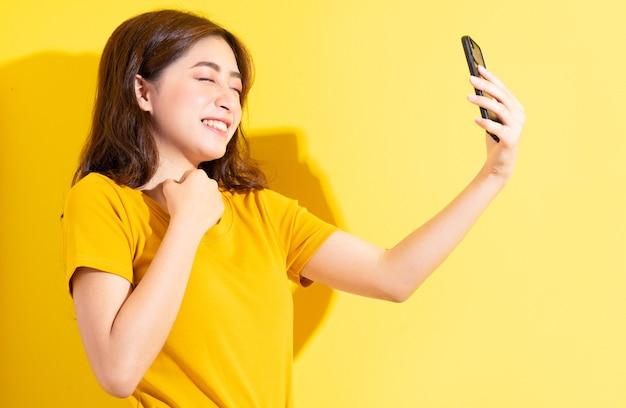 黄色の若いアジアの女の子uisngスマートフォン