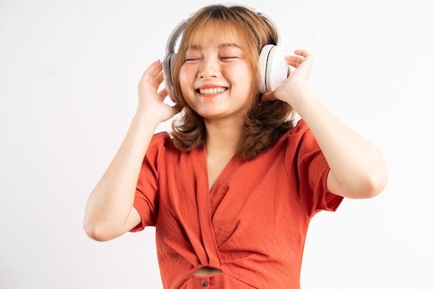젊은 아시아 소녀는 그녀의 전화를 사용하고 음악을 즐길 수있는 헤드폰을 착용