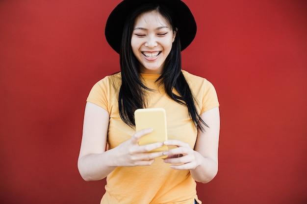 Молодая азиатская девушка с помощью мобильного телефона на улице с красной стеной - фокус на лице
