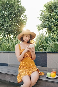 Young asian girl using smartphone at the park and wearing yellow dress with hat. summer concept.