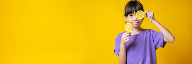 Young asian girl in violet shirt holding slice of orange,