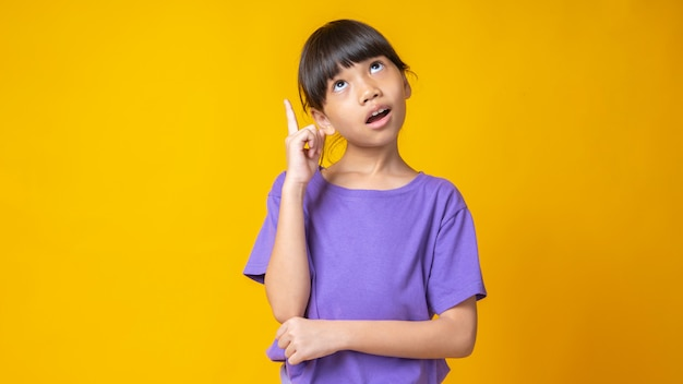 Young asian girl in violet shirt thinking and pointing up for idea,