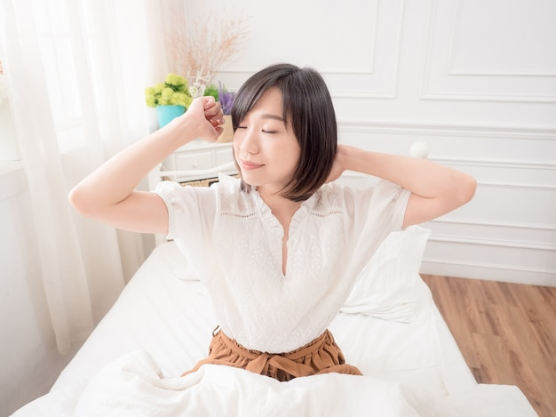 Young asian girl waking up stretching arms on the bed in the morning.