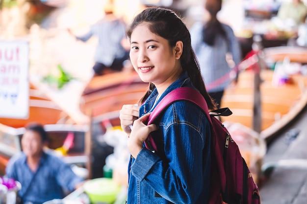 Young asian girl walking at dumonoe saduak floating market, thailand