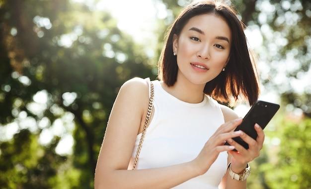 젊은 아시아 여자 공원에서 산책 하 고 사려 깊은 카메라를 찾고 모바일 휴대 전화를 사용 하여