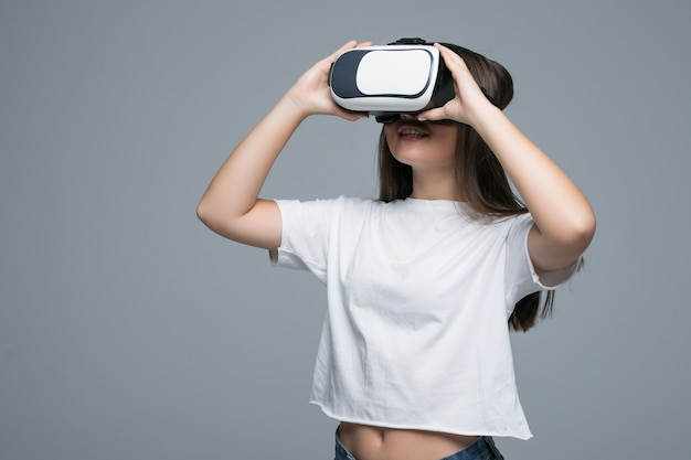 Young asian girl watching vr though and hand touch on air on gray background