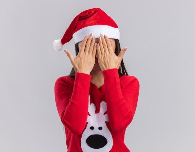 白い背景で隔離の手でセーターで覆われた顔でクリスマス帽子をかぶって若いアジアの女の子