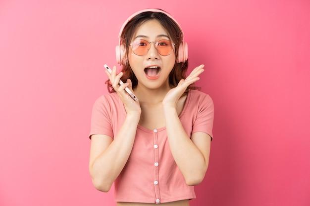 ヘッドフォンを着用し、ピンクの電話を使用して若いアジアの女の子