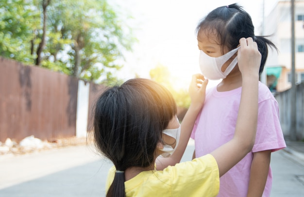 Young asian girl wearing mask for sister to protect covid 19, thai kid wear dust mask. protect pm 2.5 and stop  corona virus concept
