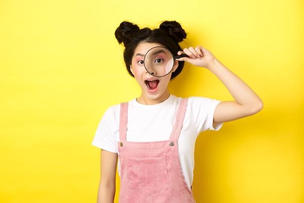 밝은 화장과 젊은 아시아 소녀는 돋보기를 통해보고 흥분 웃 고, 흥미로운 프로 모션, 노란색을보고.