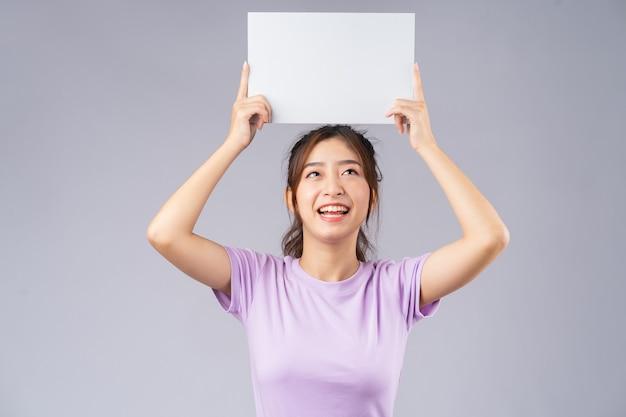 空のホワイトボードを持つ若いアジアの女の子