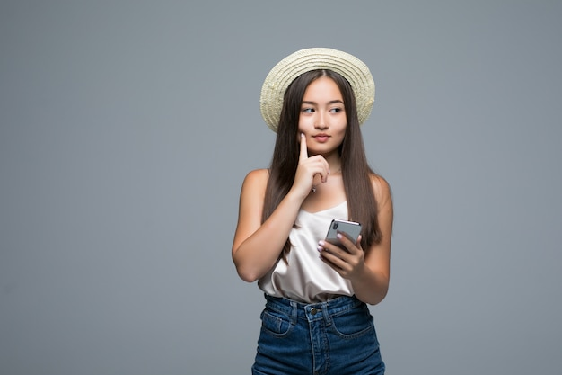 Young asian girl with straw hat use phone on gray background