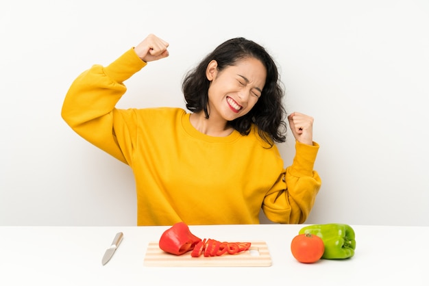 Young asian girl with vegetables in a table celebrating a victory