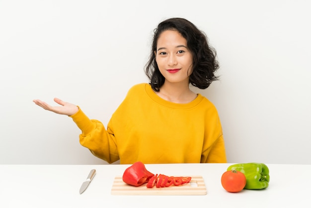 Young asian girl with vegetables in a table holding copyspace imaginary on the palm