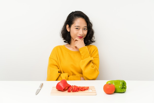 Young asian girl with vegetables in a table laughing