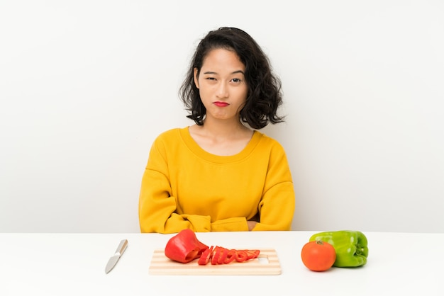 Young asian girl with vegetables in a table sad