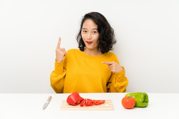 Young asian girl with vegetables in a table with surprise facial expression