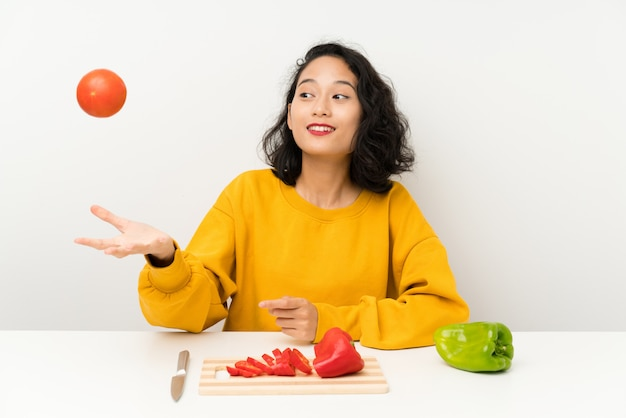 Young asian girl with vegetables in a table