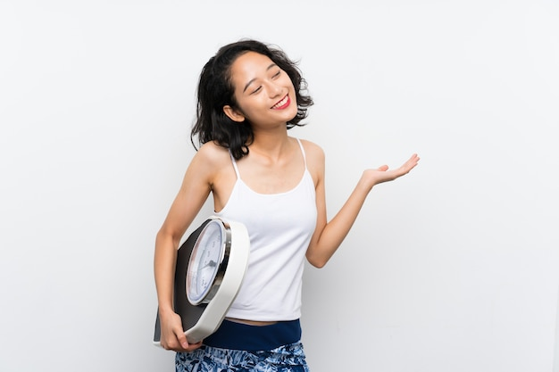 Young asian girl with weighing machine
