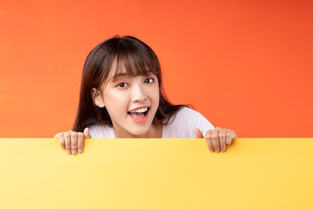 Young asian girl on yellow and orange