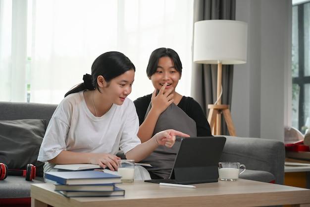 Молодые азиатские девушки выглядят возбужденными в компьютерном планшете, сидя вместе на диване