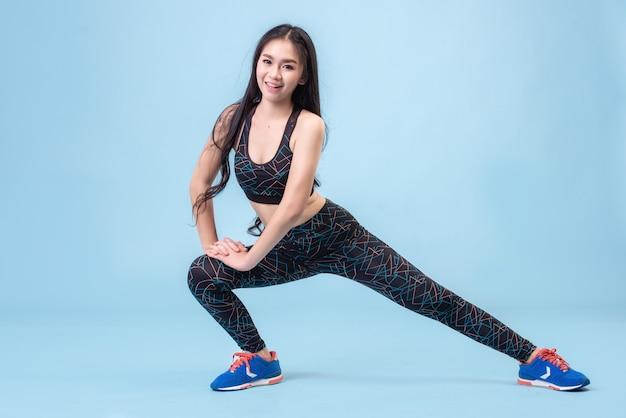 若いアジアの女の子は、パステルブルーのスタジオシーンで運動するためにレギンスを着ています。