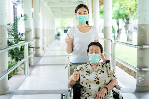 Young asian grandchild taking care her grandmother sitting on wheelchair.