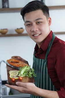 Young asian guy is happy with his business is steak shop