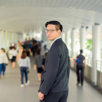 Young asian handsome businessman with his glasses standing on walkway of modern city.