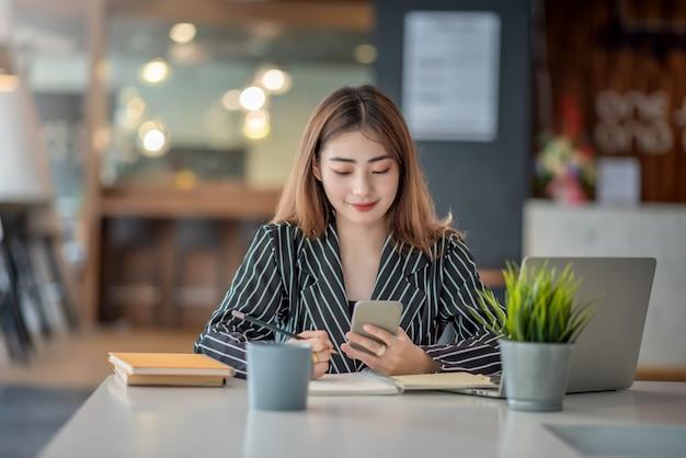 Молодая азиатская счастливая жизнерадостная коммерсантка используя смартфон в офисе.