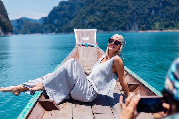 休暇中のシルクのスーツとスカーフとサングラスの若いアジアの幸せな女性ブロガー観光客は、アジアのボート、カオソック国立公園でタイを旅行します。